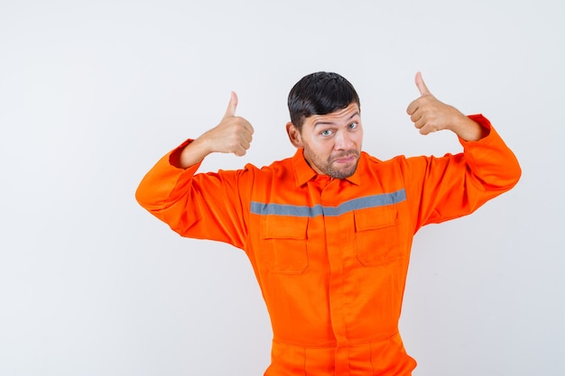 Industriële man dubbele duimen opdagen in uniform en op zoek vrolijk. vooraanzicht.