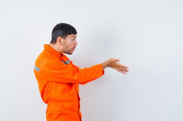 Industriële man houdt handen in vragend gebaar in uniform en kijkt verbaasd.