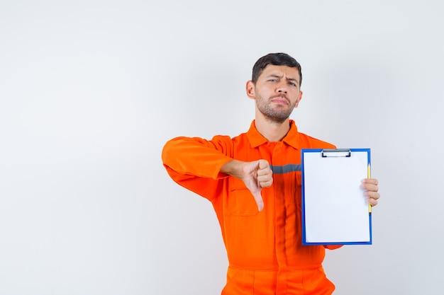 Industriële man in uniform met klembord, duim omlaag en ontevreden kijkend, vooraanzicht.