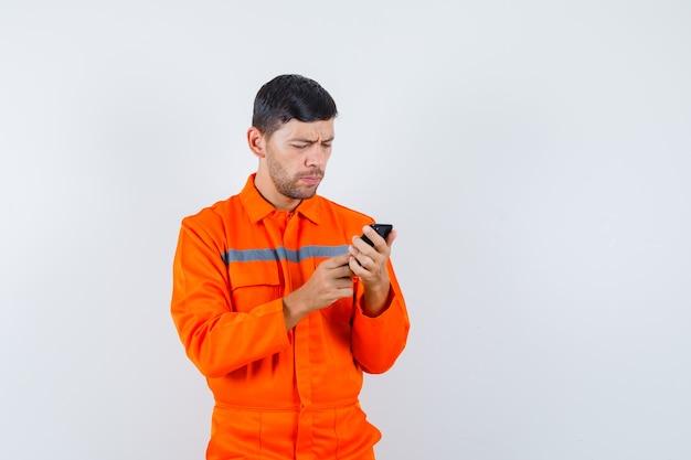 Industriële man met behulp van mobiele telefoon in uniform en op zoek naar drukke, vooraanzicht.