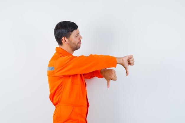 Industriële man met dubbele duimen naar beneden in uniform en ontevreden kijkt.