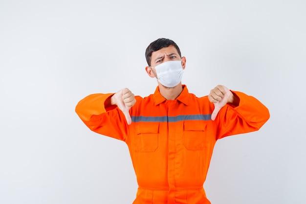 Industriële man toont dubbele duimen naar beneden in uniform, masker en kijkt ontevreden, vooraanzicht.