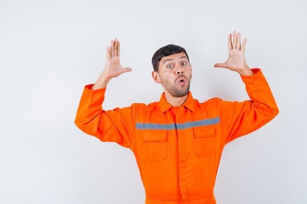 Industriële man verhogen handen in verbaasd gebaar in uniform, vooraanzicht.
