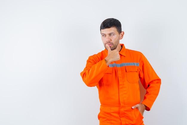 Industriële man wegkijken met vinger in lippen in uniform en peinzend op zoek. vooraanzicht.