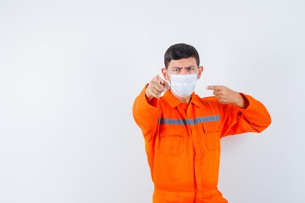 Industriële man wijst en zijn masker in uniform en kijkt serieus, vooraanzicht.