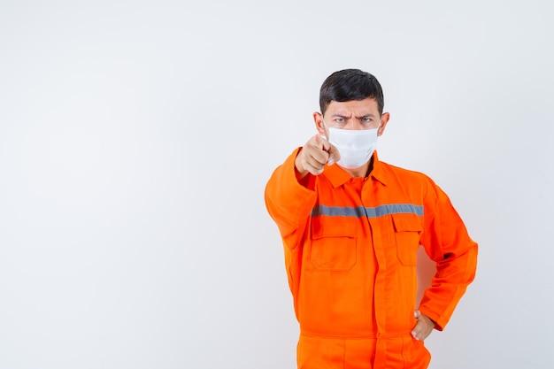 Industriële man wijst in uniform, masker en kijkt serieus. vooraanzicht.