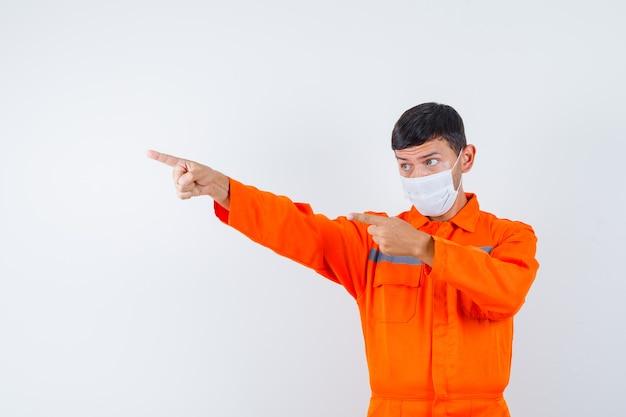 Industriële man wijst weg in uniform, masker en kijkt gefocust, vooraanzicht.