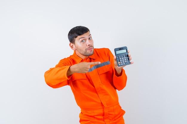 Industriële man wijzend op rekenmachine in uniform en optimistisch op zoek. vooraanzicht.