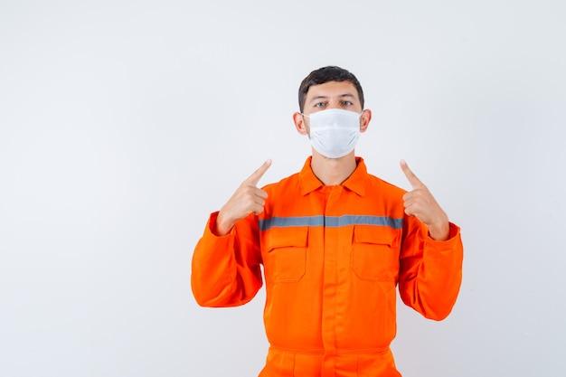 Industriële man wijzend op zijn medisch masker in uniform en kijkt voorzichtig, vooraanzicht.