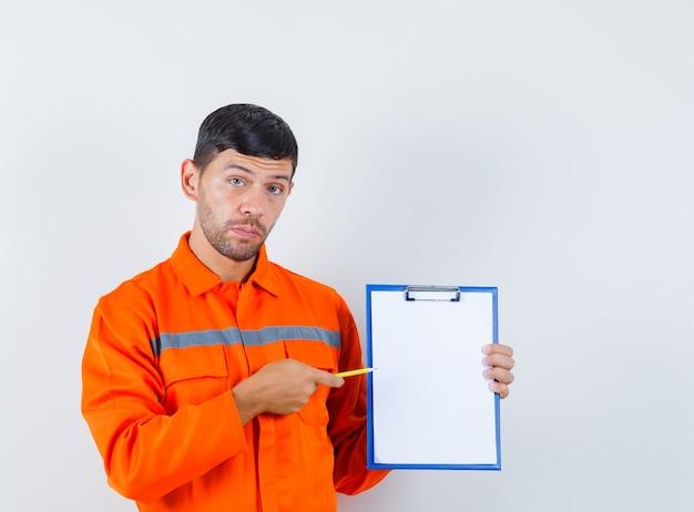 Industriële man wijzend potlood op klembord in uniform, vooraanzicht.