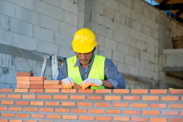 Industriële metselaar die bakstenen installeert op bouwwerf, metselaararbeider die metselwerk installeren.