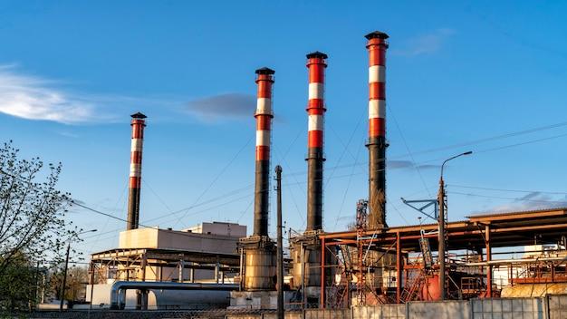 Industriële ondernemingen met pijpen tegen de blauwe lucht.