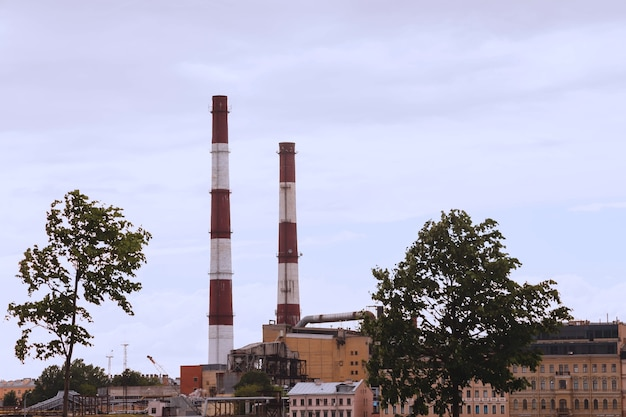 Industriële pijpen in blauwe hemel in stadscentrum. emissies van warmtepijpen. krachtpatser. lucht- en milieuverontreiniging
