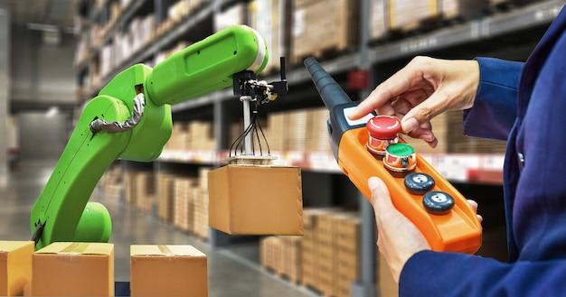 Industriële robot die een doos en arbeider houdt die een robotmachine met een controlebord op voorraadplanken in werking stellen