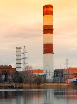 Industriële schoorsteen op de achtergrond van de zonsondergangrivier