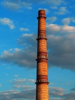 Industriële schoorsteen tijdens dramatische zonsondergangachtergrond