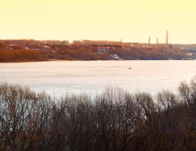 Industriële schoorstenen op rivier tijdens zonsondergangachtergrond