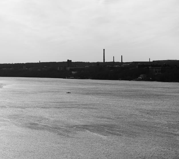 Industriële schoorstenen op rivierachtergrond
