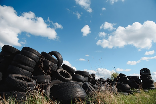 Industriële stortplaats voor de verwerking van afvalbanden en rubberbanden. stapel oude banden en wielen voor rubberrecycling