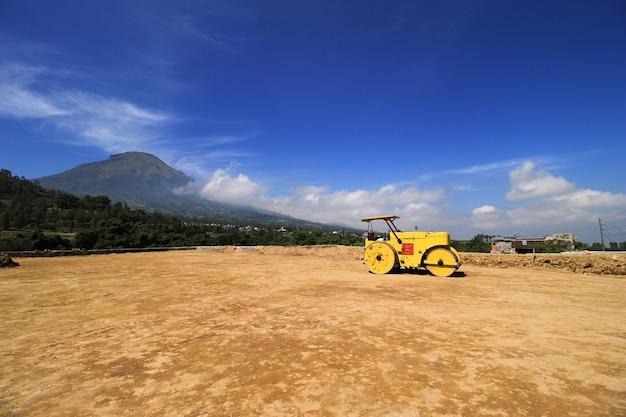 Industriële tandemrolmachine op een landnivelleringsproject