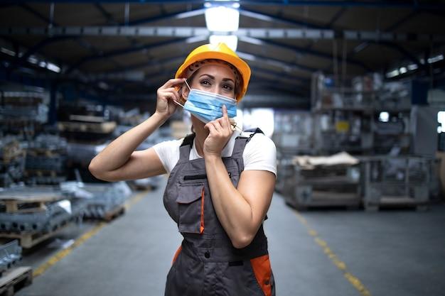 Industriële werkman staat in de fabriekshal en zet een hygiënisch masker op het gezicht om zichzelf te beschermen tegen het zeer besmettelijke coronavirus