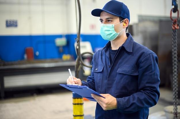 Industriële werknemer die op een document in een fabriek schrijft