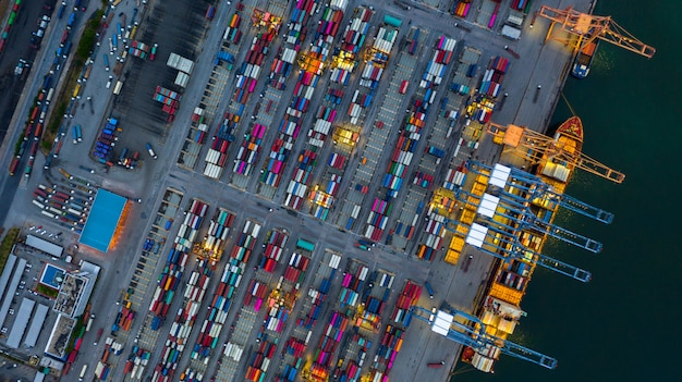 Industriële zeehaven werken 's nachts met containerschip werken' s nachts, luchtfoto containerschip laden en lossen 's nachts.