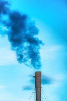 Industriële zwarte giftige rook van kolencentrale op blauwe hemel