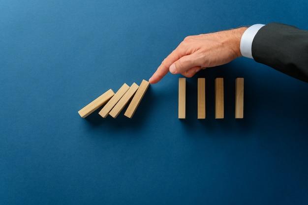 Ineenstortende domino's werden tegengehouden door mijn een crisisbedrijfsmanager in een conceptueel beeld.