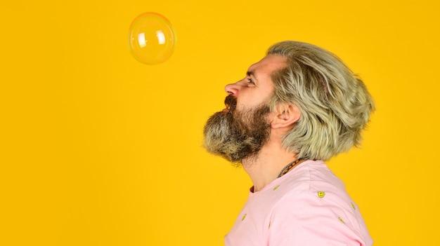 Infantiliteitsconcept vrolijke speelse bebaarde hipster en zeepbellen geluk en vreugde goede vibes