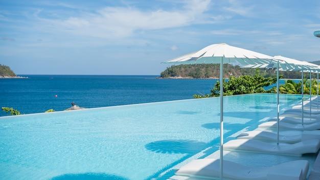 Infinity pool met parasols en zee op de achtergrond