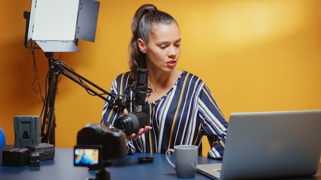 Influencer die haar publiek een nieuwe cameralens laat zien en deze beoordeelt in een professionele studioset. contentmaker nieuwe media ster influencer op sociale media pratende video-fotoapparatuur voor online internet