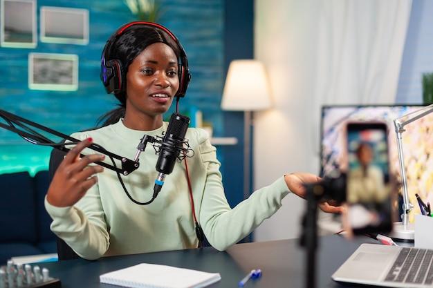 Influencer die online internetinhoud maakt voor webabonnees in de thuispodcaststudio. sprekend tijdens livestreaming, blogger discussiërend in podcast met koptelefoon op.
