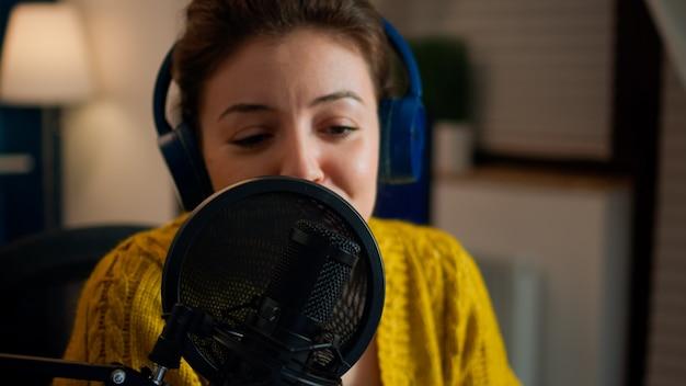 Influencer die op professionele microfoon praat tijdens livestreaming-opnamevlog in de woonkamer. on-air online productie internet uitzending show host streaming live content voor sociale media