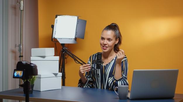 Influencer in gesprek met camera en weggeefboxen staan op het bureau klaar voor trouwe abonnees. creatieve content maker sociale media ster expert vlogger opname online internet web podcast cadeau voor au