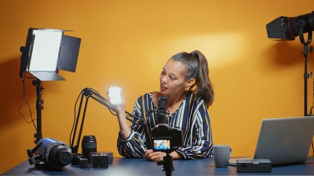 Influencer presenteert een mini-ledlamp voor professioneel gebruik in haar studio. videoblogger die een vlog opneemt met technologie die productapparatuur gebruikt in videografie en fotografie
