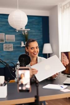 Influencer presenteert nieuwe laptop voor weggeefactie tijdens podcast. creatieve contentmaker die videoblogconcept maakt, sprekend en kijkend naar smartphone op statief bij podcast thuisstudio-uitzending