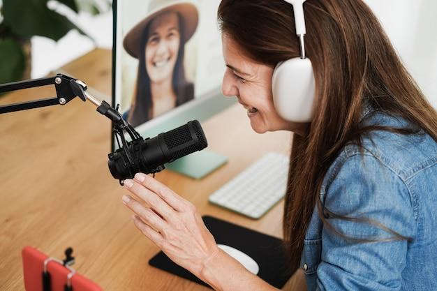 Influencer-vrouw streamt live podcast met mobiele telefoon thuis - focus bij de hand