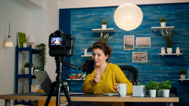 Influencer zit thuis vlogstation terwijl camera nieuwe podcast opneemt. online show on-air productie internet uitzending host streaming live inhoud, opname van digitale sociale media communicatie