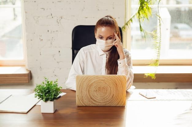Info krijgen vrouw die alleen op kantoor werkt tijdens coronavirus of covid19