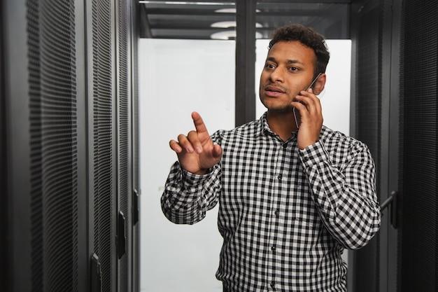 Informatie-opslag. nadenkend it-technicus praten over de telefoon en met de vinger wijzen