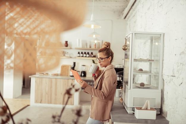 Informatiebehoefte. mooie vrouw die haar koffie drinkt en recent nieuws van haar tablet leest.