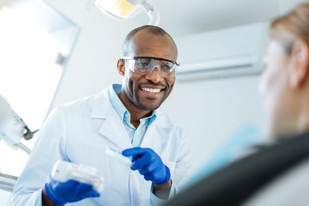 Informatieve chat. vrolijke jongeman die met zijn vrouwelijke patiënt praat en uitlegt hoe tandplak kan worden voorkomen door correct tandenpoetsen