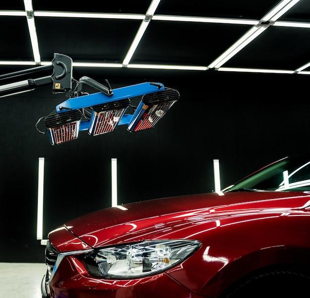 Infraroodlampen drogen een auto na het aanbrengen van een coating