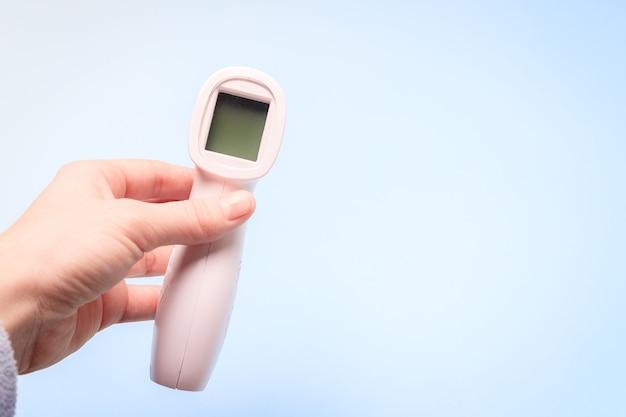 Infraroodthermometer op een blauwe achtergrond in je hand
