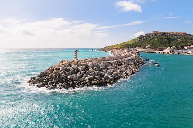 Ingang in baai, strandboulevard met vuurtoren op golfbreker. gozo, malta.