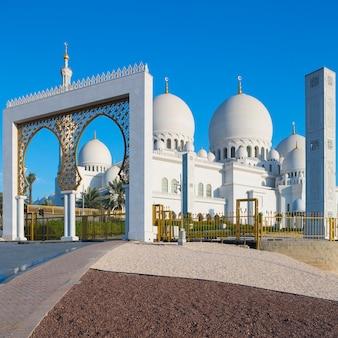 Ingang van de grote moskee sheikh zayed met blauwe hemel, verenigde arabische emiraten