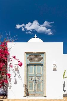 Ingang van een rustiek huis met arabische elementen en rode bloemen op de zijmuur.