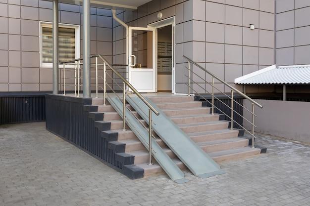 Ingangsgroep met een oprit van een woongebouw met meerdere verdiepingen trap met metalen oprit ingang van het appartementsgebouw