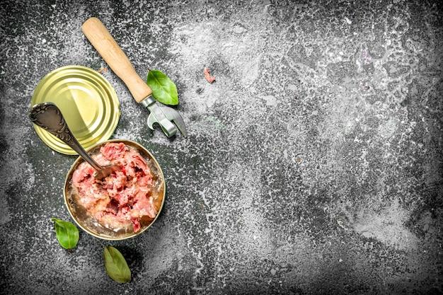 Ingeblikt vlees in een blikje op rustieke tafel.